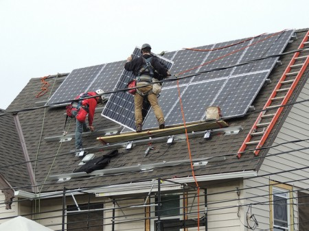 Contractors install solar panels to make the renovated house more energy efficient. (Photo courtesy of LBWN)