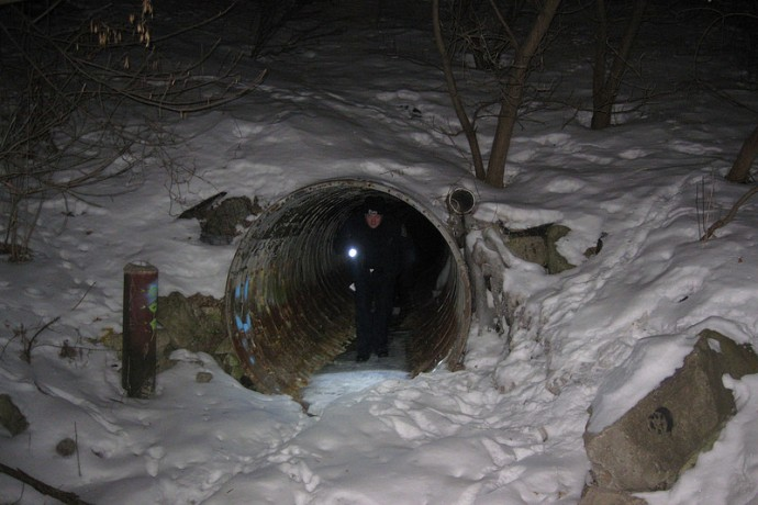 Milwaukee police officer James Knapinski walks out of a rain tunnel near the Milwaukee River on the city's near north side as he searches for the homeless. (Photo by Brendan O'Brien)