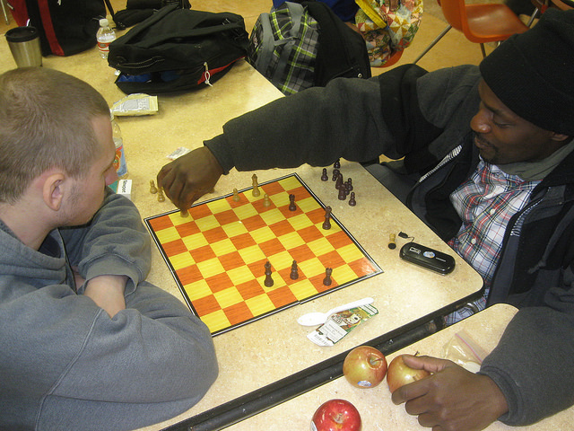 Brian Schoenfeldt (left) and Omar McGee play chess at the St. Benedict the Moor warming center, 1015 N. 9th St. (Photo by Brendan O'Brien)