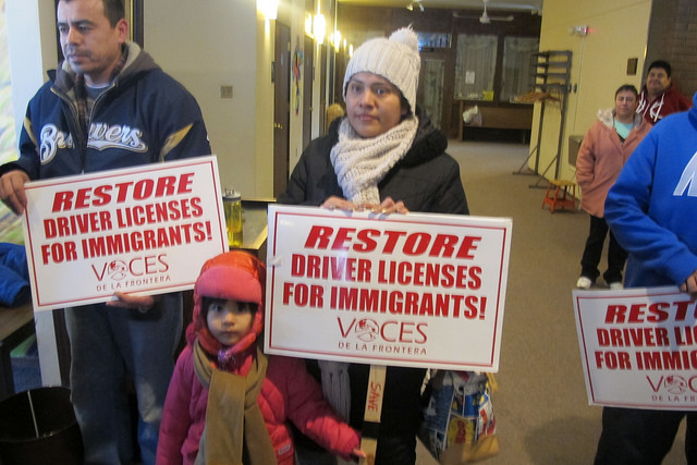 Advocates from Voces De La Frontera held signs supporting the driver's license measure. (Photo by Edgar Mendez)
