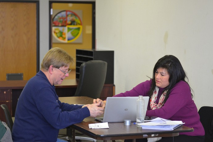 Lisa Anderson, a health care specialist at the Gerald L. Ignace Indian Health Center, helps Ronald Graef, 59, get insurance on Healthcare.gov, the website for the Affordable Care Act marketplace. (Photo by Sue Vliet)