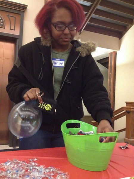 Jbri Seay, a launch party attendee, selects free condoms provided by 414ALL.