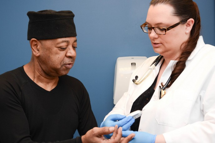 Litisha Ramus, a family nurse practitioner at Milwaukee Health Services' Convenient Care Clinic, tests the blood of patient Tony Driver. (Photo courtesy of Milwaukee Health Services)