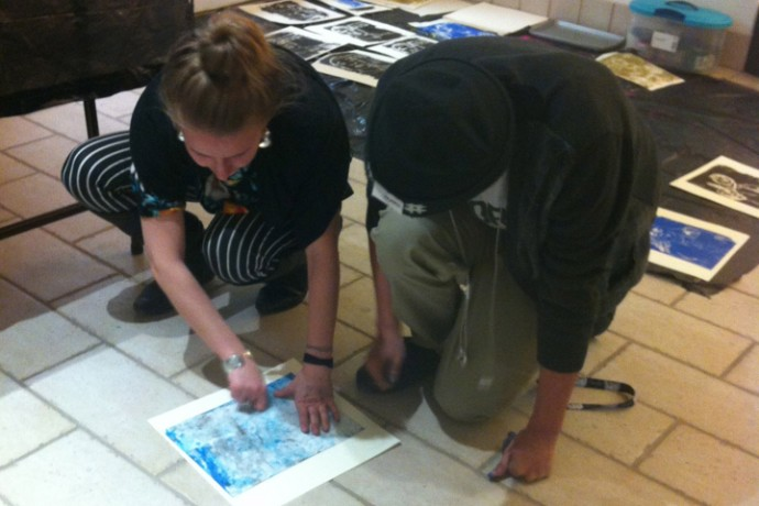 Lead artist Kim Loper works with a student on his print project.