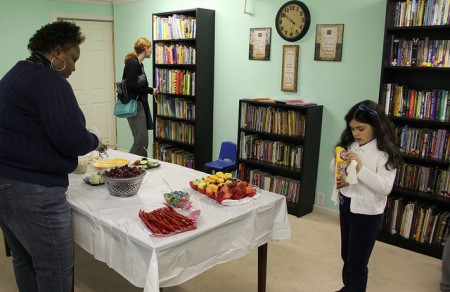 Volunteers Michele Watson and Dayanara Sanchez prepare for the celebration of the new reading room created for clients at Meta House. (Photo by Karen Slattery)