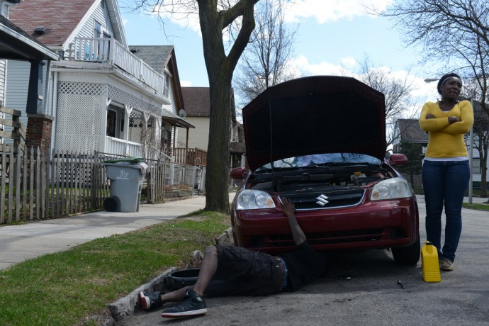 Mitchell Aaron performs auto maintenance on Michelle Taylor's maroon Suzuki sedan. (Photo by Sue Vliet)
