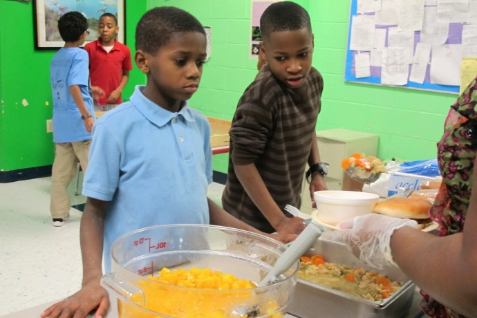 Children line up at a free meal program. (Photo by Tessa Fox)