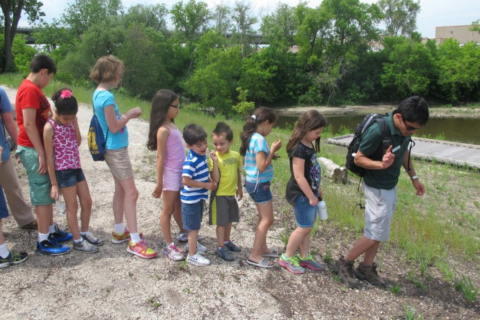 Martin Ponce, a volunteer at the Urban Ecology Center Menomonee Branch, leads a group of children in the Young Scientists Club down an eroded hill. (Photo by Edgar Mendez)