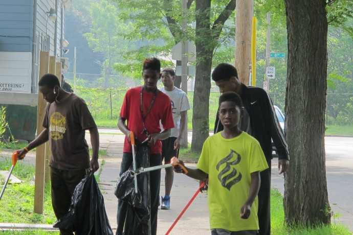 Teens pick up garbage in their neighborhood, employed by community activist Andre Lee Ellis. (Photo by Karen Stokes)
