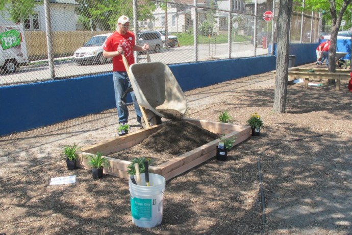 A Target volunteer builds a raised-bed garden on the playground at Doerfler School. (Photo by Patrick Leary)