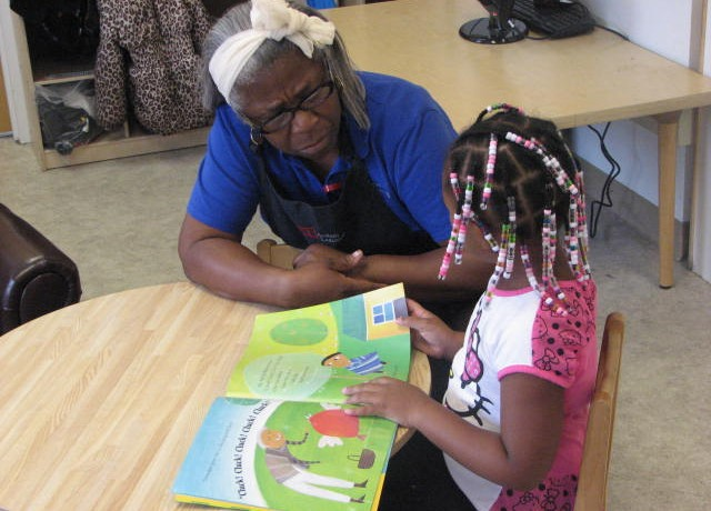 Acelero teacher Benedicta Graves reads a book with one of her students. (Photo by Patrick Leary)