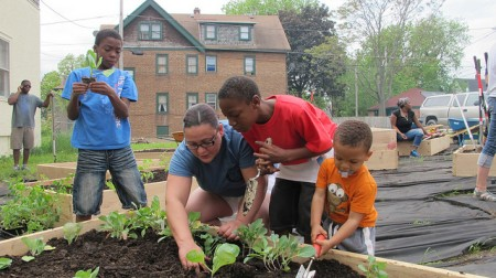 From left: William Clary, Heidi Sutton, Daiquizion James and Sutton's nephew, Cortez Hodges, plant vegetables at a community garden in Metcalfe Park last summer. (Photo by Andrea Waxman)