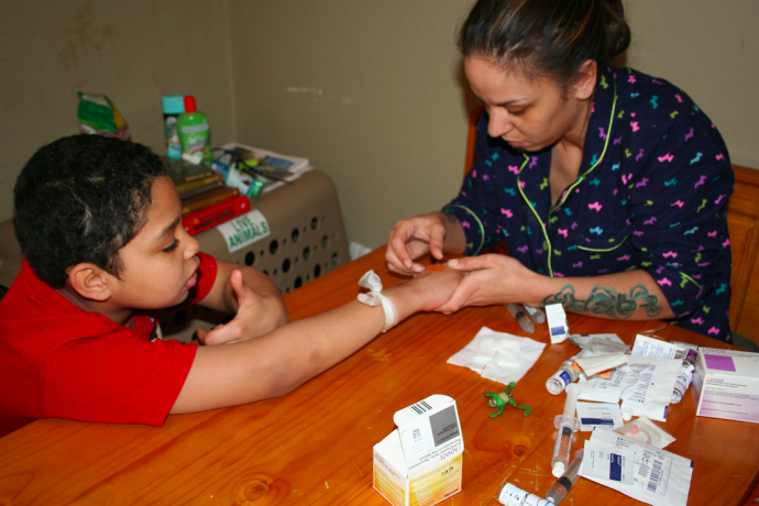 Danielle Suchla carefully administers her son's medication. (Photo by Jenna Ebbers)