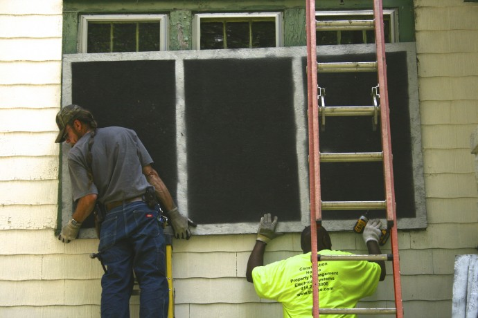 (left) Paul Buettner and Derrick Williams from T.L. Reese Corp. put up painted boards. (Photo by Hannah Byron)