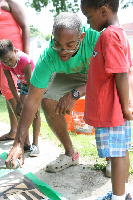 Anwar Floyd-Pruitt, project coordinator for Painting with Purpose, shows local youth how to spray paint boards using stencils. (Photo by Hannah Byron)
