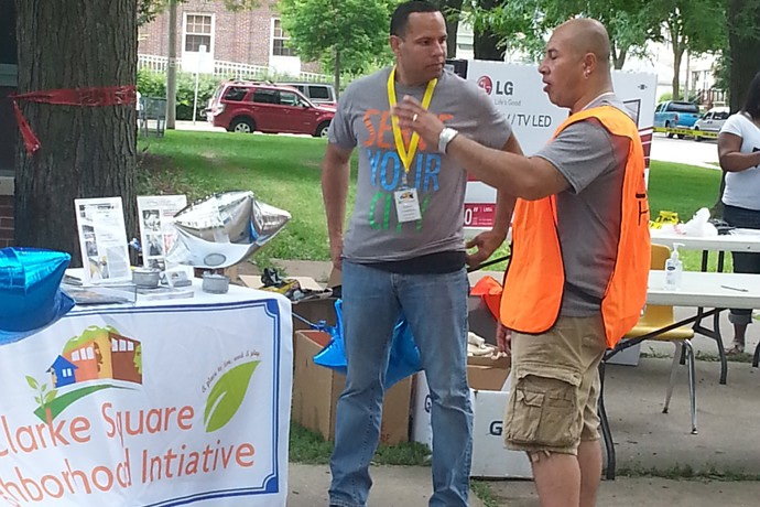 Ramon Candelaria, executive director of the Clarke Square Neighborhood Initiative, chats with volunteer Anthony Mercado during Serve Your City Day.