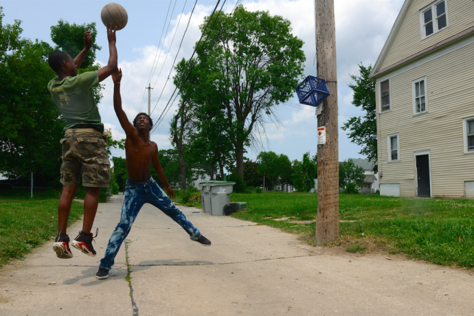 Deonta Grimes, 13, takes a jumper over his cousin Latravius Gregory, 16, during a pick-up game. (Photo by Sue Vliet)