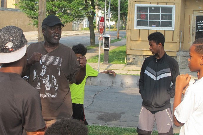 Andre Lee Ellis gives advice and encouragement to some of the young men who came to work in the community garden. (Photo by Andrea Waxman)