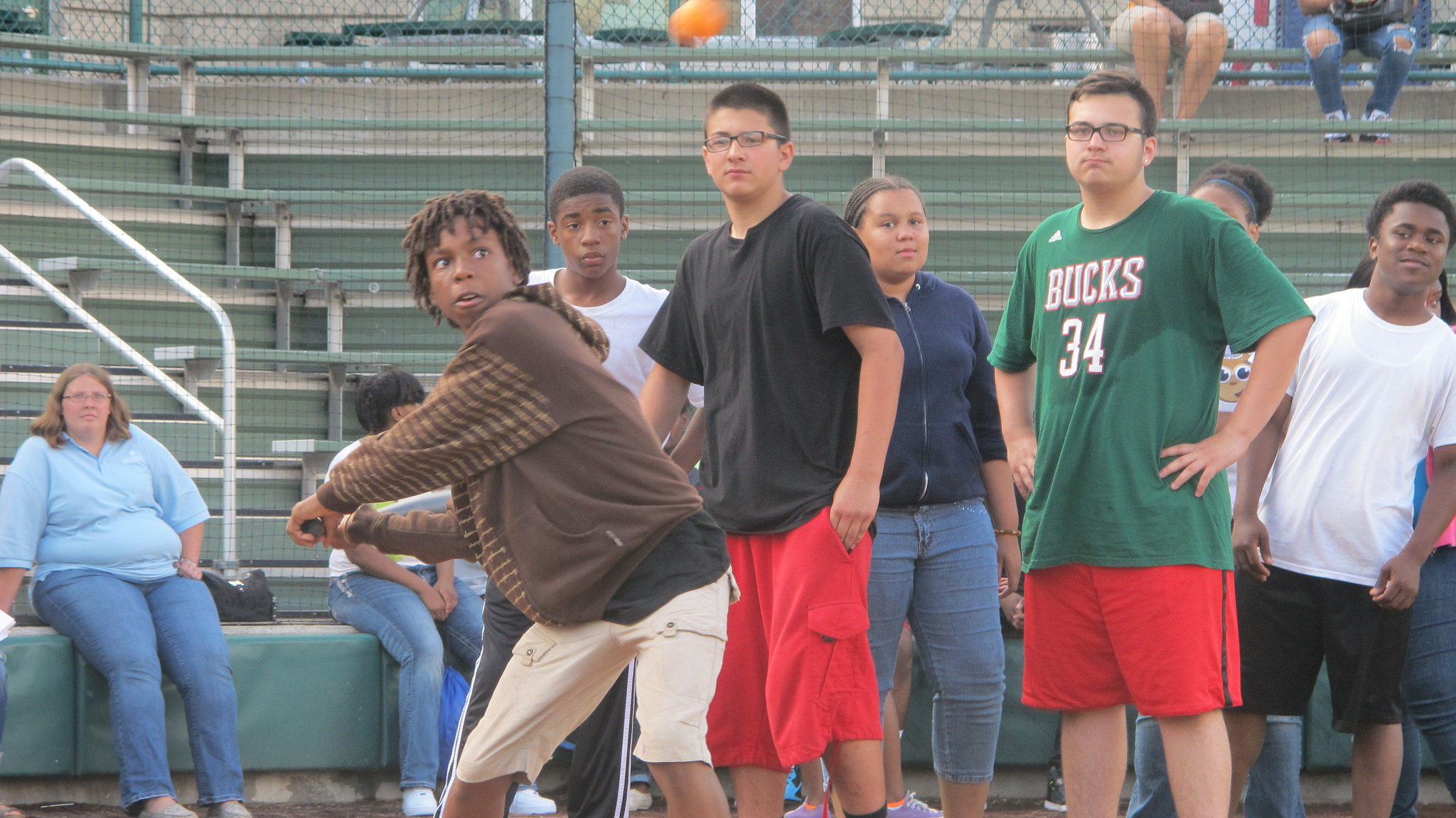 Kids from Agape Community Center swing the bat during the high-tempo game of Quickball. (Photo by Scottie Lee Meyers)