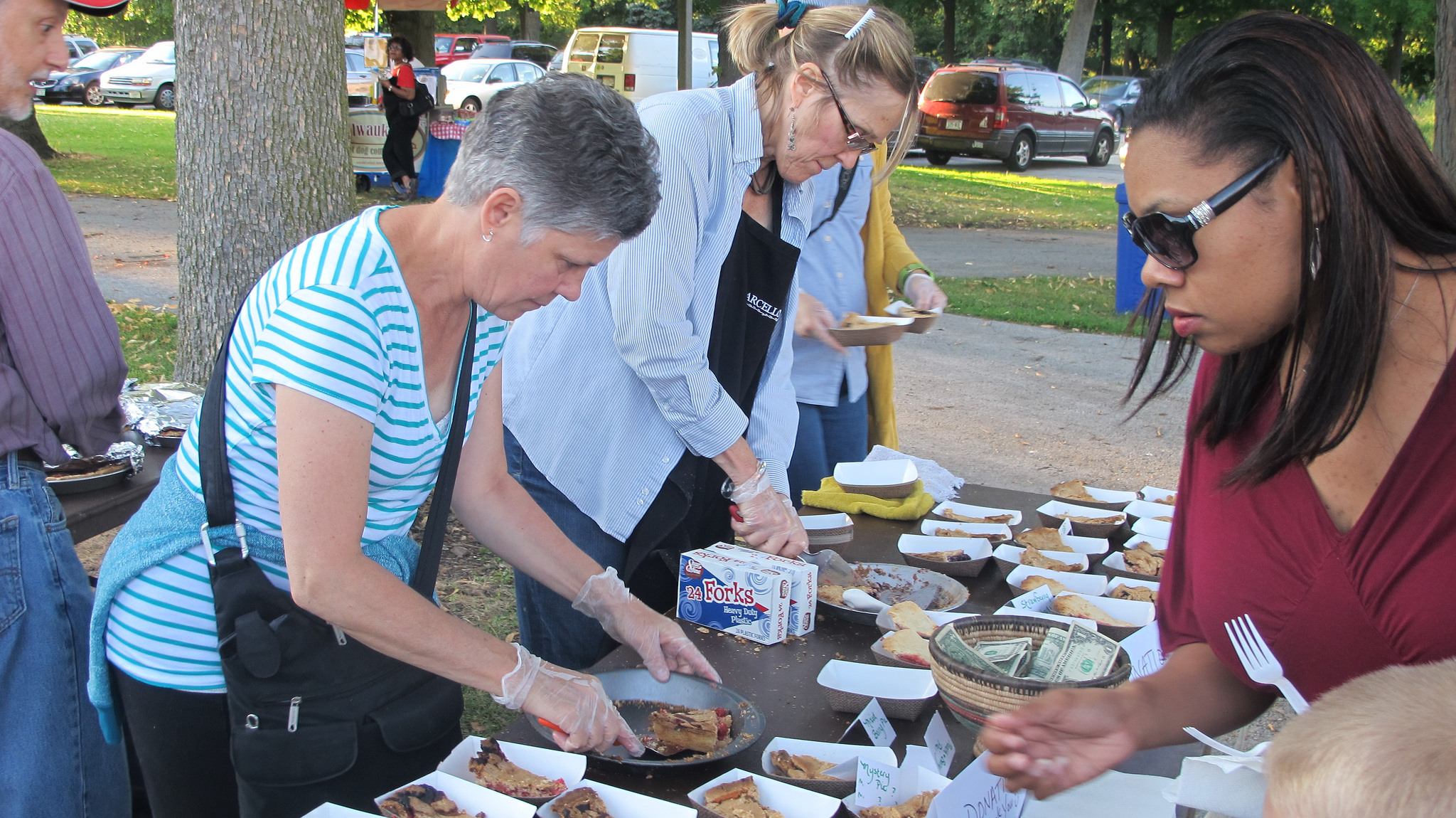Volunteers cut and serve pie at a recent Wednesday at the Shell concert in Washington Park. (Photo by Andrea Waxman)