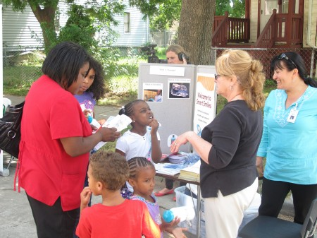 A young girl shows off her teeth at a dental hygiene booth at the I Have a Dream Foundation block party. (Photo by Patrick Leary)