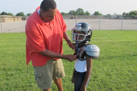 Rodney Hudson helps his son, Rodney, Jr. , with his shoulder pads. (Photo by Edgar Mendez)