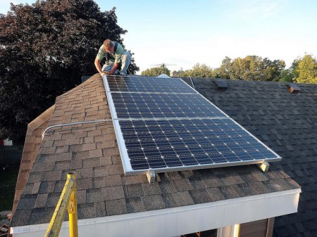 Workers install solar energy equipment on a roof in the Burnham Park neighborhood. (Photo courtesy of Layton Boulevard West Neighbors)
