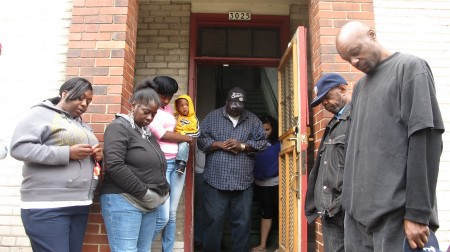 People bow their heads during a prayer before Adullam Outreach opens its doors. (Photo by Brendan O'Brien)