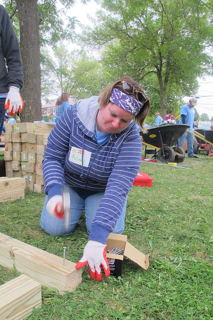 Volunteer Kristy Currie an associate from CarMax helps build a piece of playground equipment. (Photo By Raina J. Johnson)