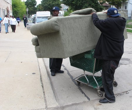 A man attempts to use a plastic grocery cart to take a home a couch that he just picked up at Adullam Outreach's warehouse. (Photo by Brendan O'Brien)