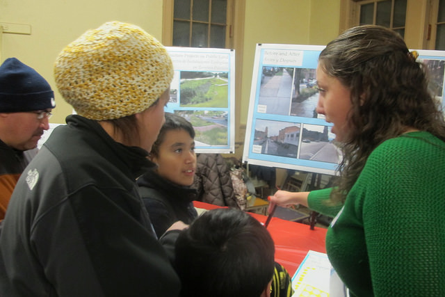 Nadia Bogue, environmental project coordinator at the Sixteenth Street Community Health Center, discusses possible changes to Pulaski Park with residents at a recent open house. (Photo by Edgar Mendez)