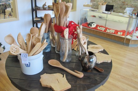 A display at Our Daily Salt features handcrafted wooden spoons, including the Happy Spoon, and a Wisconsin-shaped cutting board. (Photo by Raina J. Johnson)