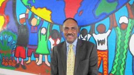 PACA Executive Director Fessahaye Mebrahtu stands near a mural designed by immigrant and refugee children at the Pan African Community Association.  (Photo by Andrea Waxman)