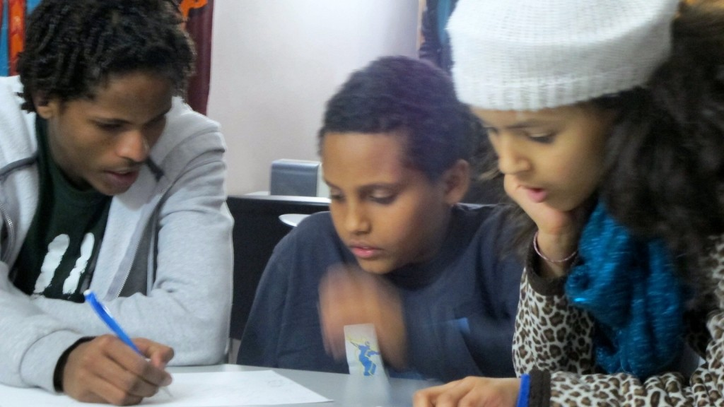 (From left) Filimon Hailu, 17, tutors Mulubrhan Yosief, 9, and Saron Weldemariam, 10, during an after-school session at the Pan-African Community Association. (Photo by Andrea Waxman)