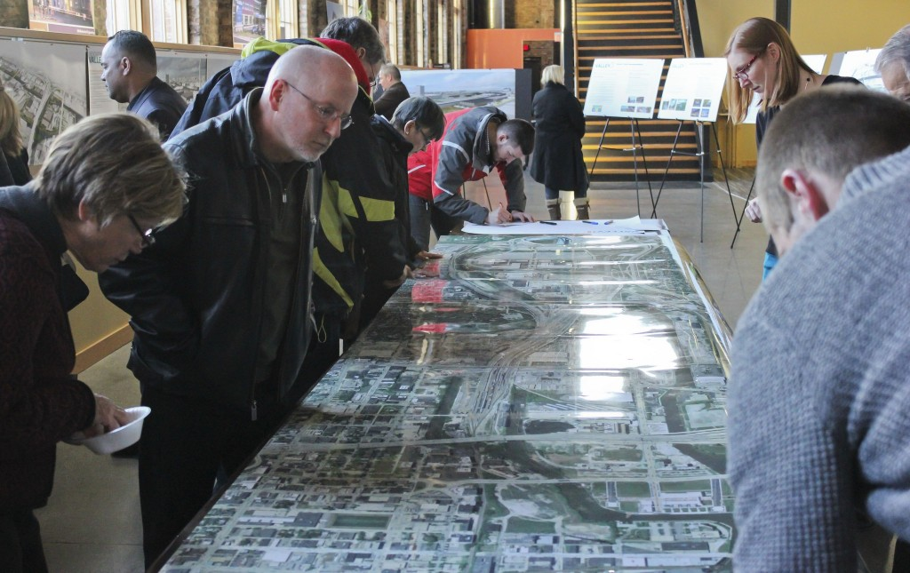 Visitors pore over an aerial map at an open house to preview development of the Menomonee Valley, held at the Zimmerman Architectural Studios. (Photo by Alhaji Camara)