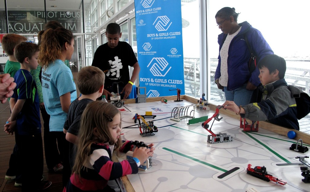 Michael Quezada, coach of the Davis Boys & Girls Club all-girls team, demonstrates a Lego robot at Discovery World. (Photo by Devi Shastri)