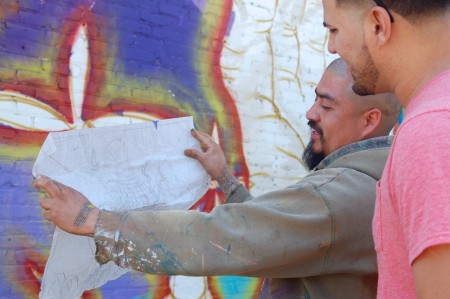 Artist Ramiro Arguta shows Eli Crespo the initial sketch of the mural's design. (Photo by Devi Shastri)