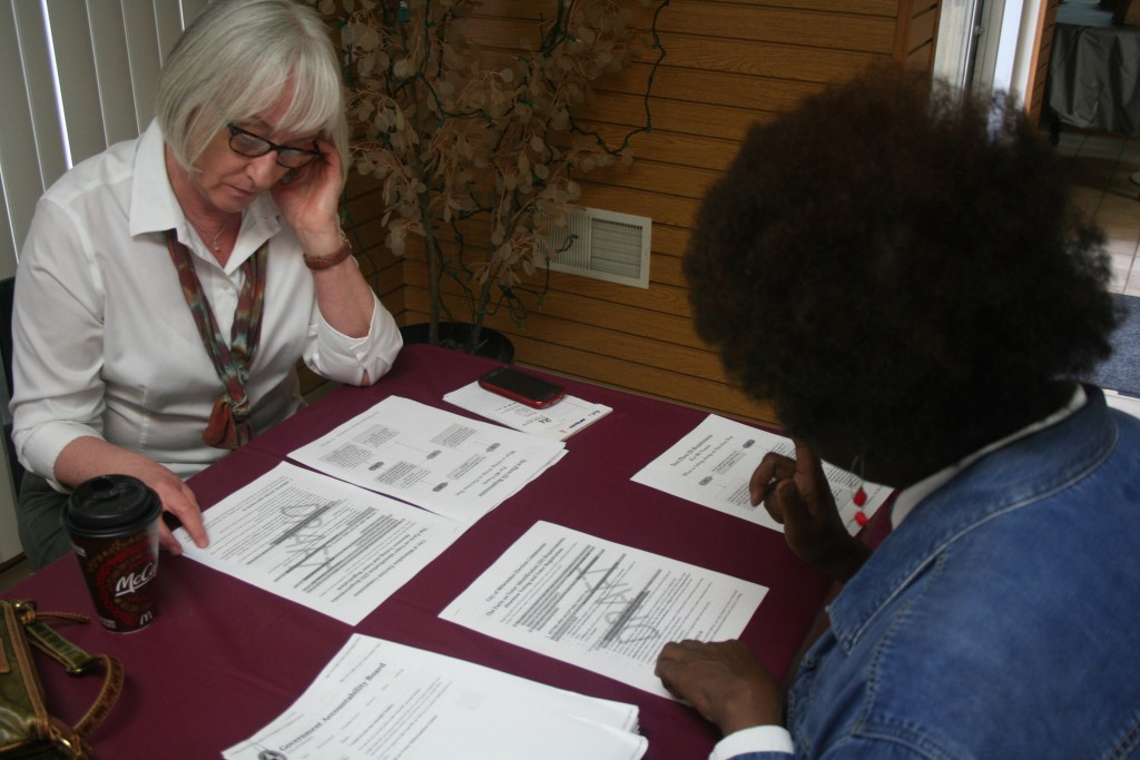 Anita Johnson (right) takes Janice Erickson through a list of voter ID requirements, as outlined by the Milwaukee Election Commission. (Photo by Jabril Faraj)