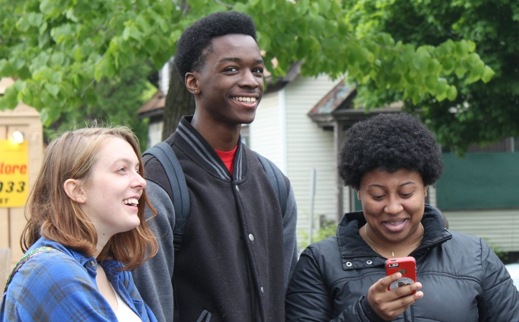 Mikey Murray, right) reads one of her poems on her phone as fellow Wisconsin slam poetry champions Caide Jackson (left) and Jonnie Dixon look on. (Photo by Matthew Wisla)
