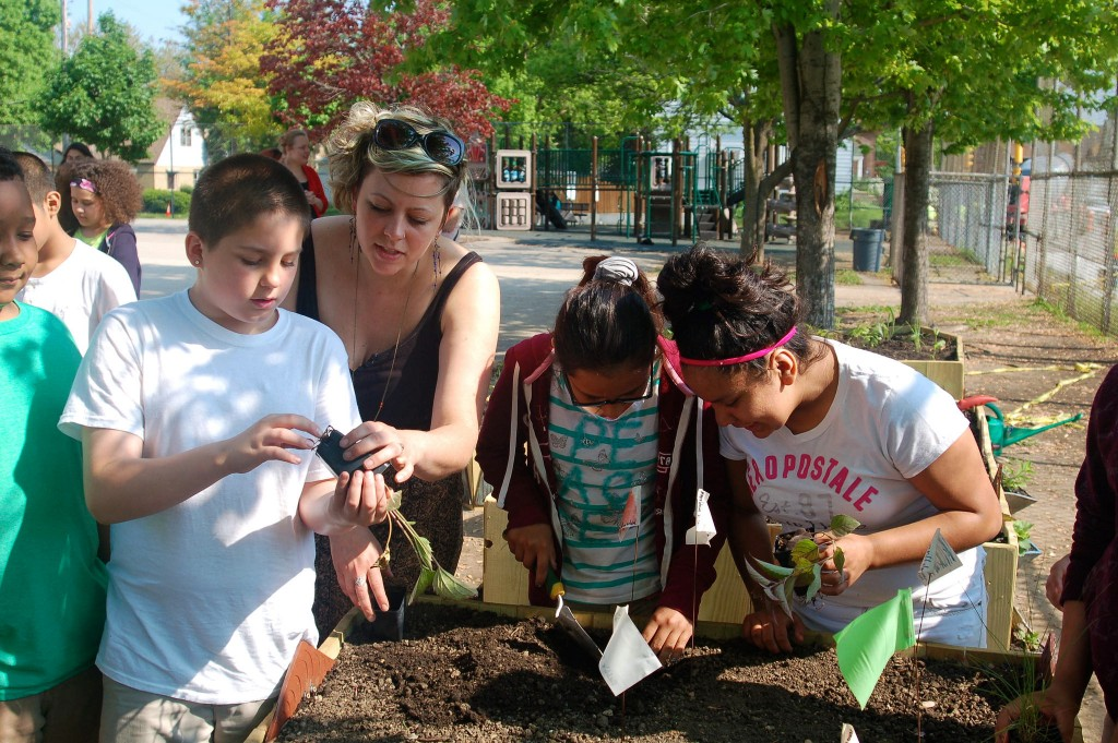 Ceramics artist Janelle Gramling helps 4th-grade students put the finishing touches on their garden at Greenfield Bilingual School.