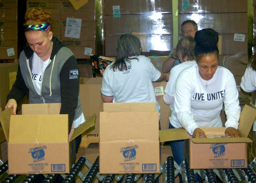 Nearly 25 volunteers pack new books into boxes for the Summer Slide reading program.