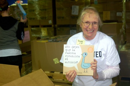 Charlene Stevens holds up a popular title before placing it in the box to be distributed in the coming months. (Photo by Allison Dikanovic)