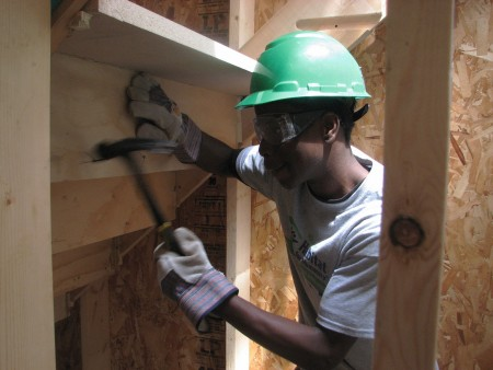 YouthBuild participant Curtis Thomson pounds a nail into a staircase as he helps build a Milwaukee Habitat for Humanity home. (Photo by Brendan O'Brien)