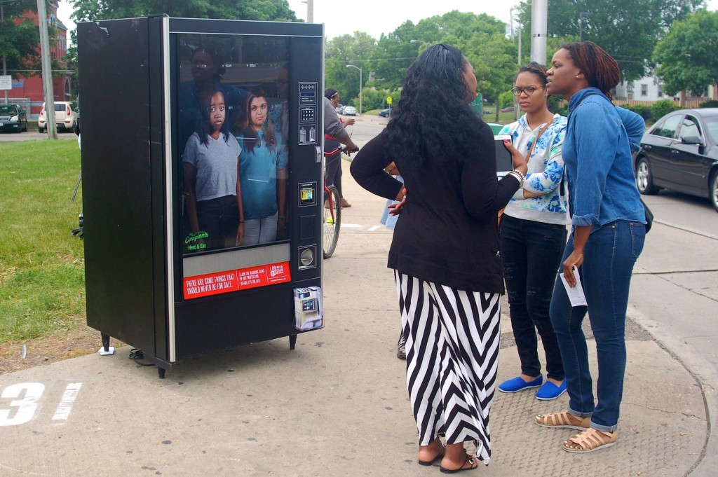 Social worker Jasmine Whiting speaks with young people passing the Children Are Not For Sale awareness campaign in front of a vending machine on North Ave. and 27th St. (Photo by Allison Dikanovic)
