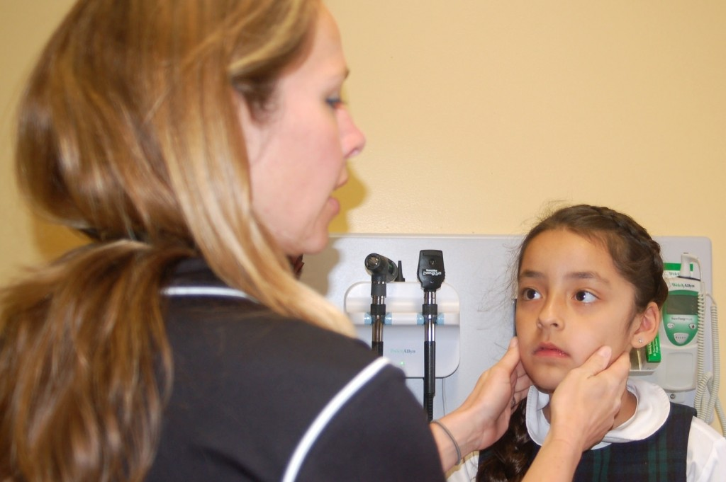 Padre Pio Clinic director Dana Rodriguez examines a second grader. (Photo by Devi Shastri)