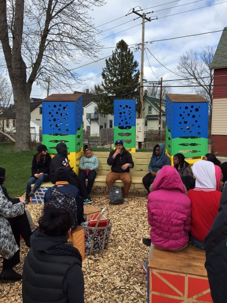 A.W.E. board member Adam Carr (center) is the first to tell a story in the Story and Art Garden at 9th and Burleigh streets, with LaFollette Boys & Girls Club members in the audience. (Photo by Andrea Waxman)