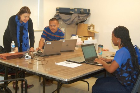 Project Coordinator Sarah O'Connor and Community Health Specialists Fue Xiong and Yvette Ssempijja look at data. (Photo by Devi Shastri)