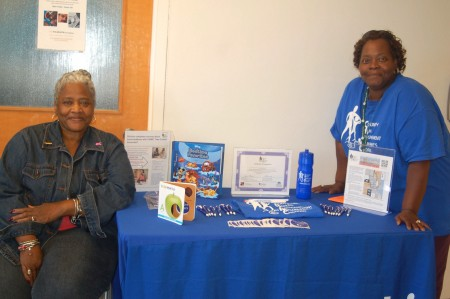 Community Forward Team members Carolyn Ramsey and Janice Hurrell stand at the recruiting table. (Photo by Devi Shastri)