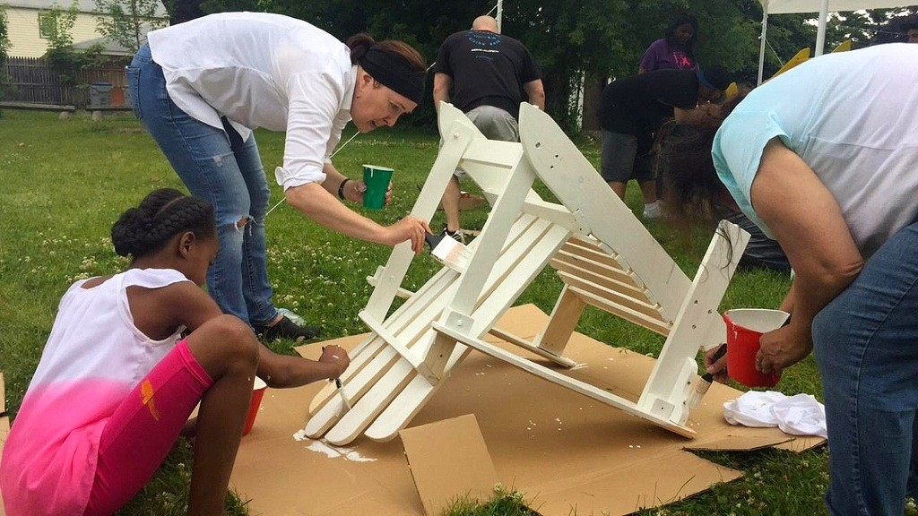 Karen Mierow paints an Adirondack chair with Thurston Woods residents as part of the Yellow Chair Project.