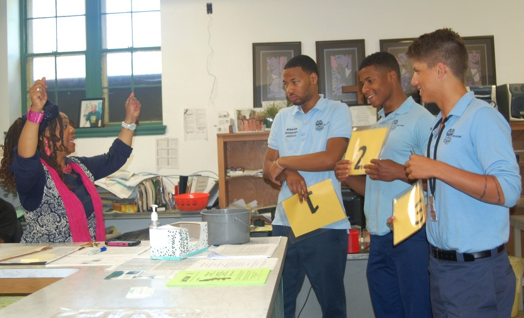 Pastor Teresa Thomas-Boyd demonstrates to Police Ambassadors Anthony Rodriguez, Kalin Welch and Michael Hendrix how to hold up numbers to call up visitors. (Photo by Devi Shastri)